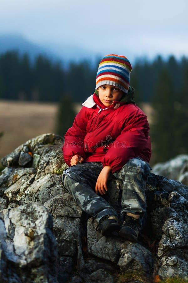 Caminhante da criança que senta-se no penhasco fotografia de stock