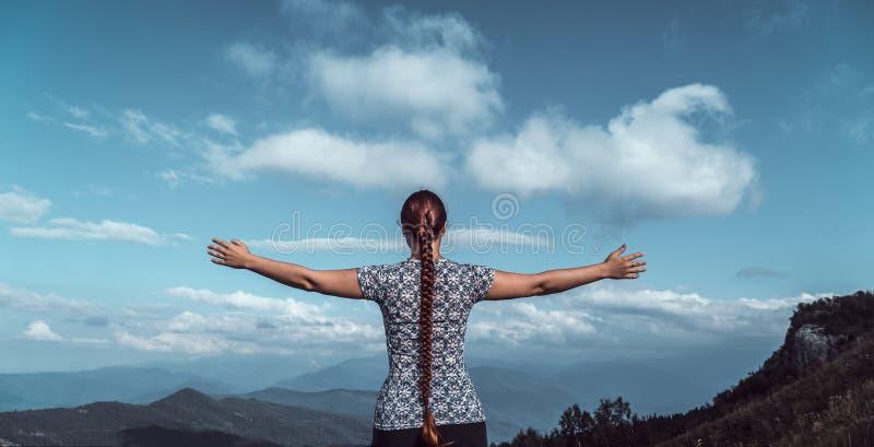Caminhante da jovem mulher com os braços abertos no pico de montanha, conceito da liberdade, foto panorâmico imagens de stock royalty free