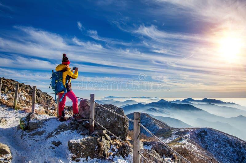 Caminhante da jovem mulher que toma a foto com o smartphone no pico de montanhas foto de stock