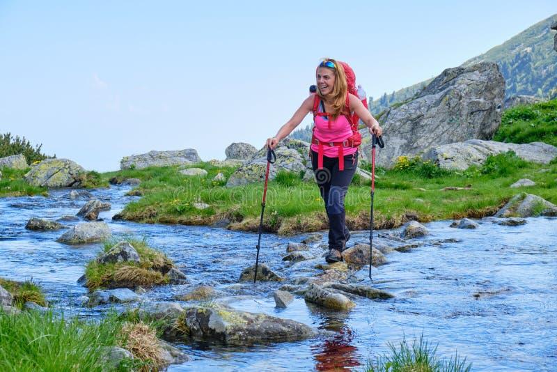 Caminhante da jovem mulher, rindo ao cruzar uma associação natural da infinidade pisando em rochas do rio, com uma trouxa vermelh fotos de stock royalty free