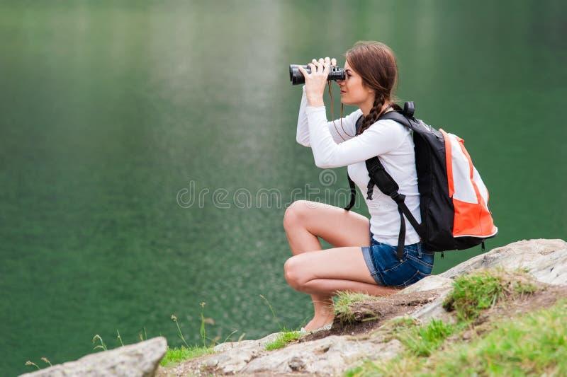 Caminhante da jovem senhora com a trouxa que senta-se na montanha imagens de stock royalty free