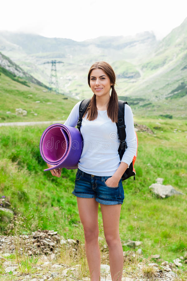 Caminhante da jovem senhora com a trouxa que senta-se na montanha foto de stock royalty free