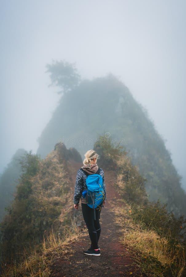 Caminhante da mulher com a trouxa no trajeto enevoado estreito do cume da montanha na ilha de Santo Antao, Cabo Verde imagem de stock