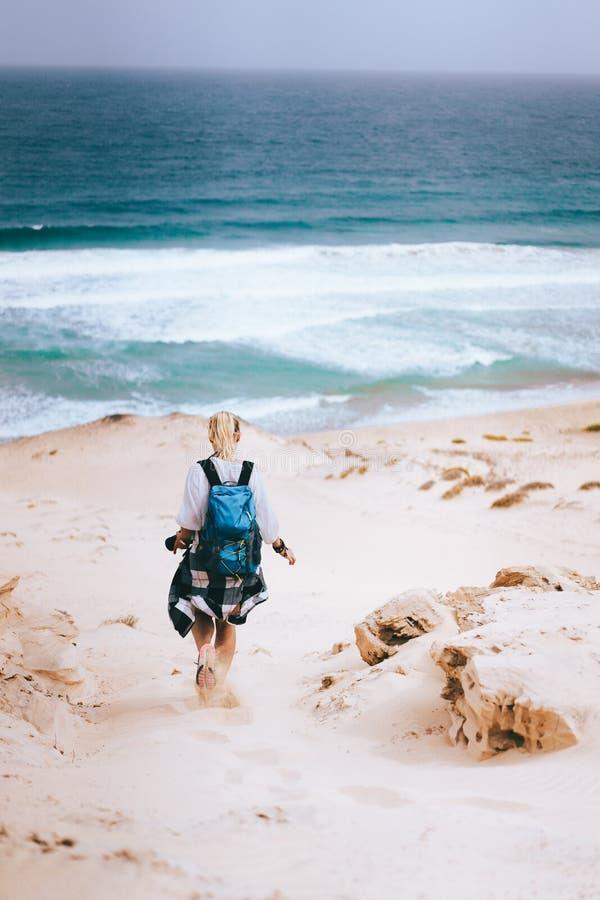 Caminhante da mulher com a trouxa que vai abaixo de uma duna de areia para a praia só Sao Vicente Cape Verde imagem de stock