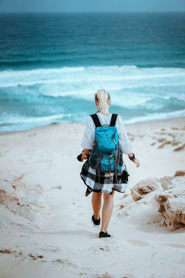 Caminhante da mulher com a trouxa que vai abaixo de uma duna de areia para a praia só Sao Vicente Cape Verde imagem de stock royalty free