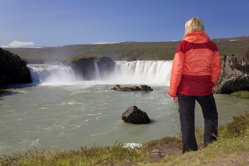 Caminhante da mulher na cachoeira de Godafoss, Islândia foto de stock
