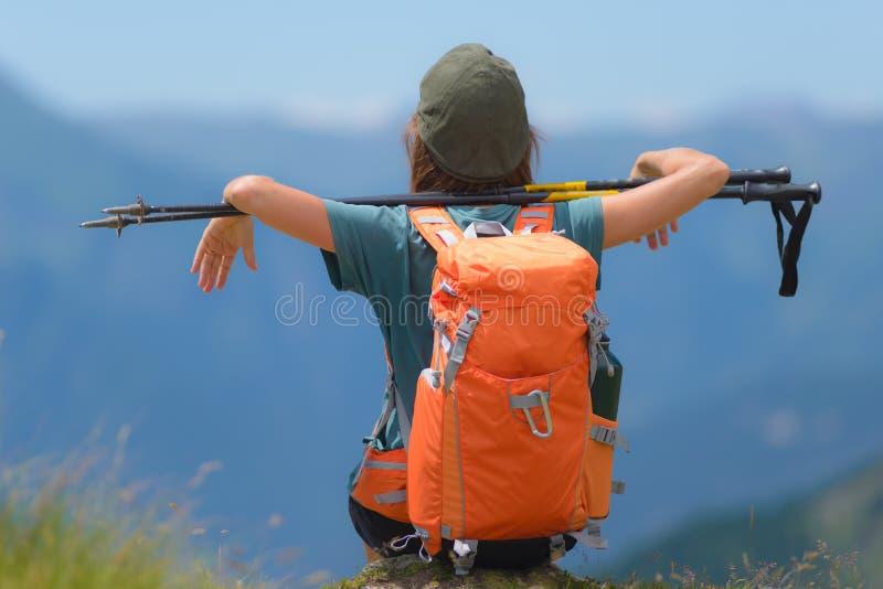 Caminhante da mulher na parte superior da montanha com trouxa e polos trekking, opinião traseira de foco seletivo, cumes no fundo foto de stock royalty free