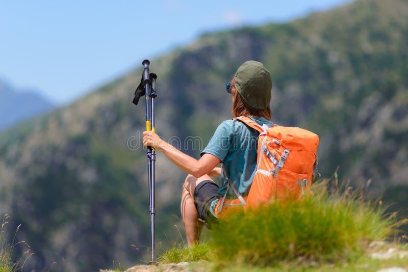 Caminhante da mulher na parte superior da montanha com trouxa e polos trekking, opinião traseira de foco seletivo, cumes no fundo imagem de stock