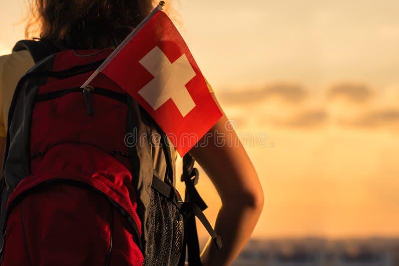 Caminhante da mulher na parte superior da montanha no short e de um t-shirt com uma trouxa e na bandeira de Suíça em um fundo do  fotos de stock royalty free