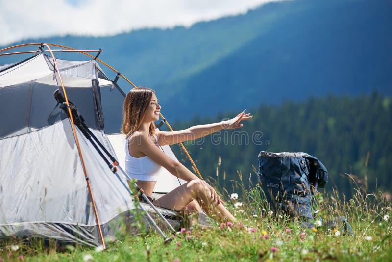 Caminhante da mulher no acampamento nas montanhas com a trouxa na manhã imagens de stock