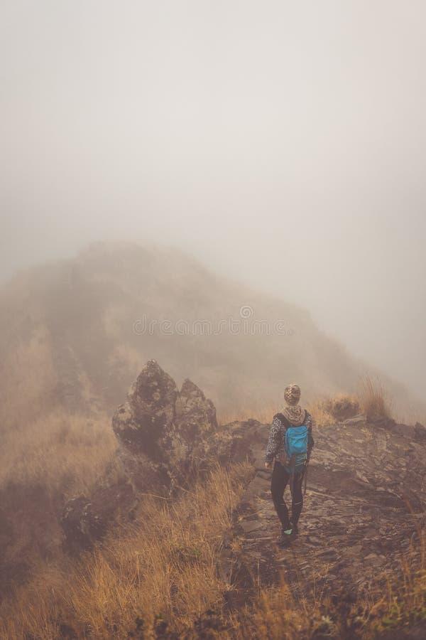 Caminhante da mulher no trajeto enevoado cobbled na crista de montanha na ilha de Santo Antao, Cabo Verde foto de stock royalty free
