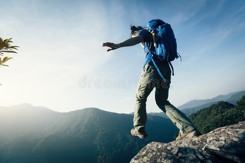 Caminhante da mulher que anda à borda do penhasco na parte superior da montanha foto de stock