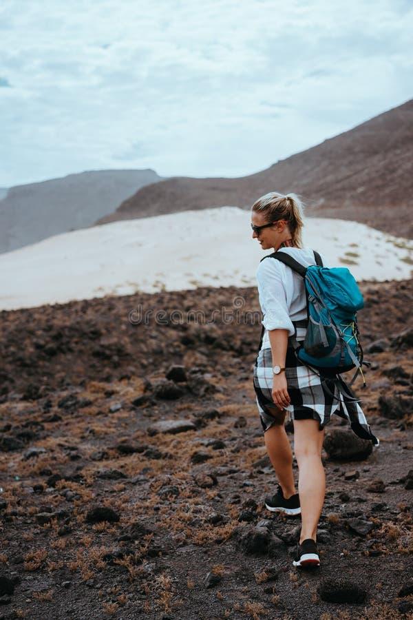 Caminhante da mulher que anda no terreno rochoso estéril entre pedregulhos vulcânicos pretos e as dunas de areia brancas Sao Vice foto de stock