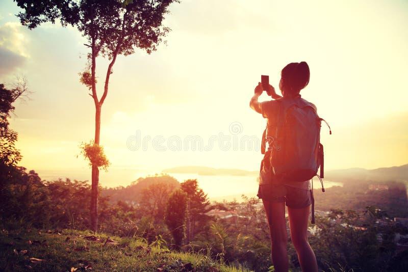 Caminhante da mulher que toma a foto com câmara digital fotografia de stock