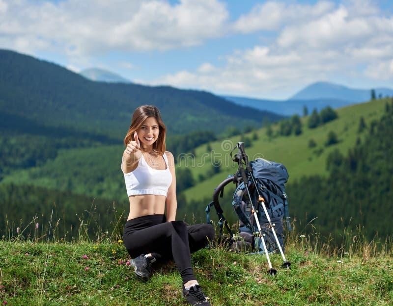 Caminhante desportivo da mulher com a trouxa que descansa nas montanhas fotos de stock royalty free