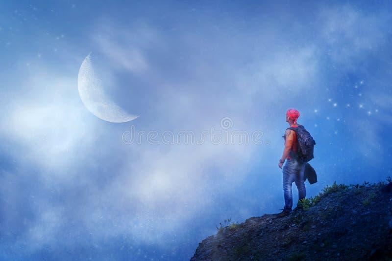 Caminhante desportivo do indivíduo com uma trouxa na borda do penhasco contra um céu azul com estrelas e lua Conceito do curso e  fotos de stock