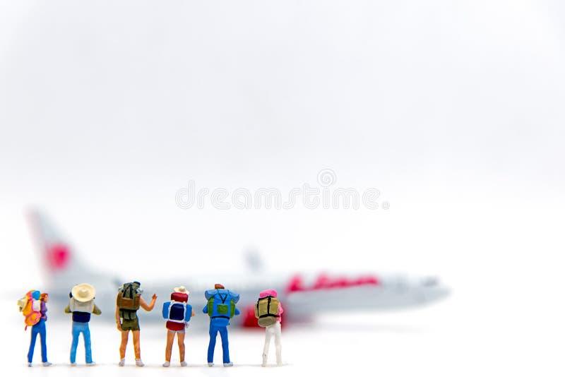 Caminhante diminuto e viajante do grupo com trouxa que andam ao avião no mapa do mundo com espaço da cópia para o curso em todo o fotografia de stock royalty free