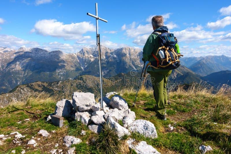 Caminhante do homem, perto do rood da parte superior, na parte superior da montanha olhando o mo fotografia de stock royalty free