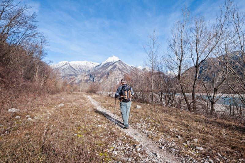 Caminhante do homem que anda na fuga sobre a costa do rio para montanhas foto de stock royalty free