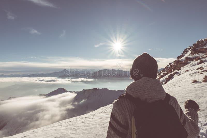 Caminhante do mochileiro da mulher que olha a vista alta acima nos cumes A vista traseira, neve fria do inverno, sol protagoniza  foto de stock