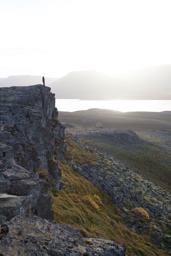 Caminhante em um penhasco rochoso durante o por do sol Grande atmosfera com fotos de stock