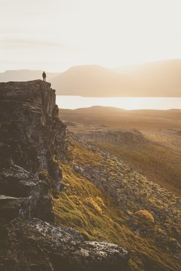 Caminhante em um penhasco rochoso durante o por do sol Grande atmosfera com imagens de stock