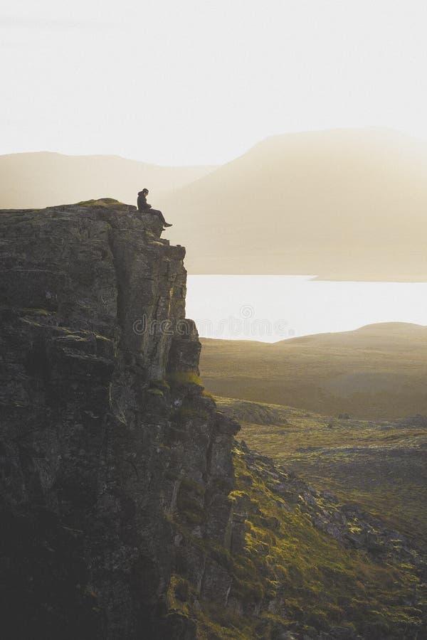Caminhante em um penhasco rochoso durante o por do sol Grande atmosfera com fotografia de stock