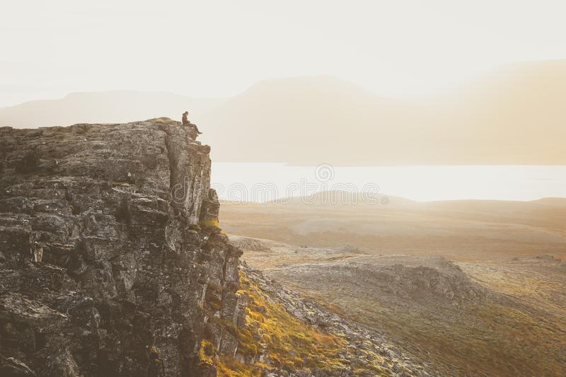 Caminhante em um penhasco rochoso durante o por do sol Grande atmosfera com imagem de stock