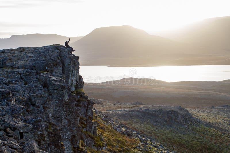 Caminhante em um penhasco rochoso durante o por do sol Grande atmosfera com fotografia de stock royalty free