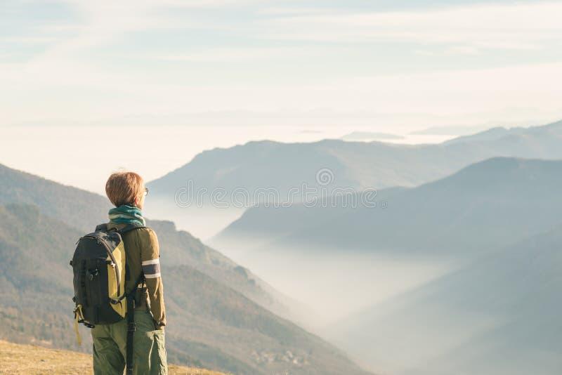 Caminhante fêmea com a trouxa que olha a vista majestosa nos cumes italianos Névoa e névoa no vale abaixo, montanha snowcapped fotos de stock