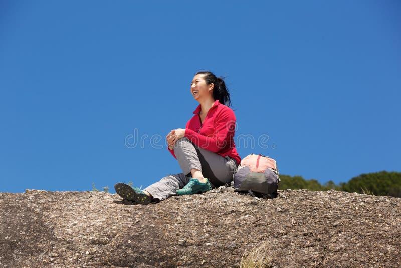 Caminhante fêmea de sorriso que senta-se na rocha e em apreciar a vista imagem de stock