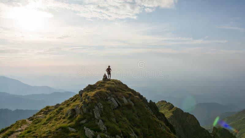 Caminhante fêmea novo que olha sobre o vale da parte superior da montanha no por do sol imagens de stock royalty free