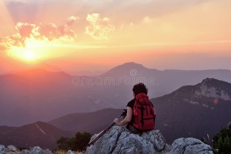 Caminhante fêmea que descansa e que olha o por do sol fotos de stock royalty free