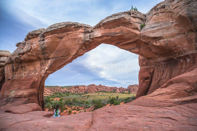 Caminhante fêmea sob arco quebrado, parque nacional Moab Utá dos arcos imagens de stock