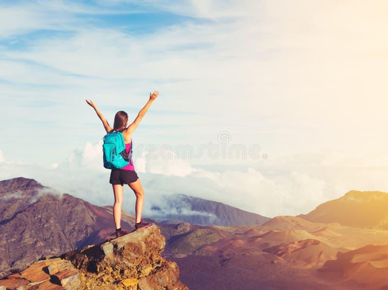 Caminhante feliz da mulher com os braços abertos no por do sol no pico de montanha imagens de stock royalty free