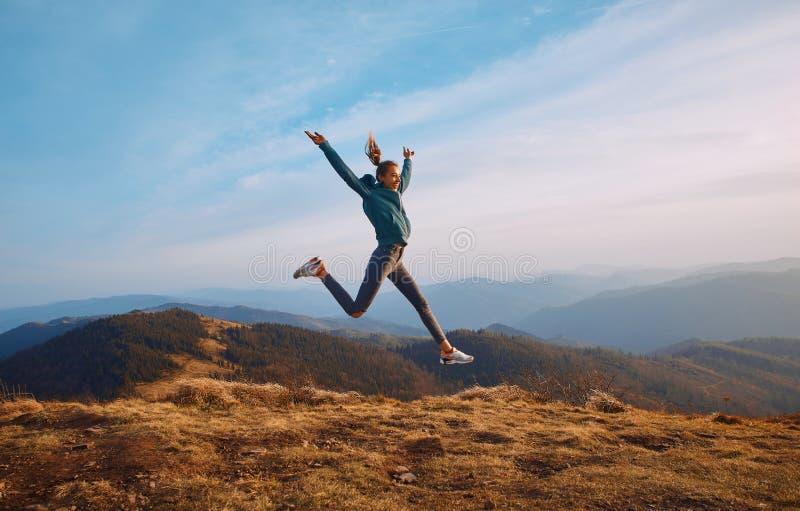 Caminhante feliz da mulher que salta no cume da montanha no fundo azul do céu nebuloso e das montanhas imagens de stock