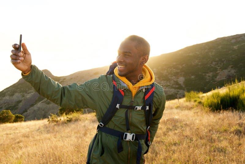 Caminhante masculino afro-americano novo considerável que toma o selfie com telefone celular foto de stock