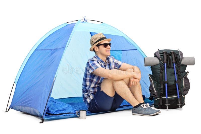 Caminhante masculino alegre que senta-se na frente de uma barraca fotos de stock royalty free