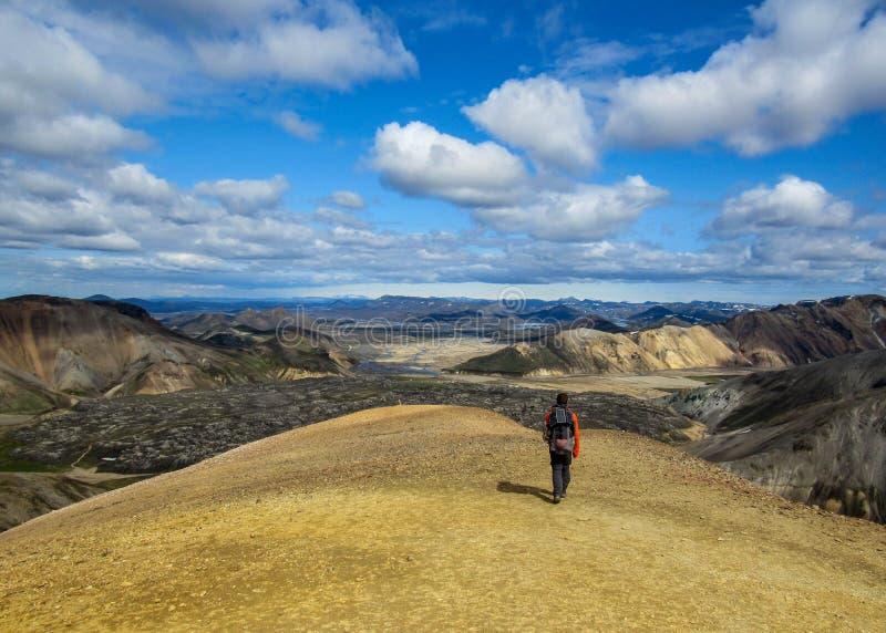 Caminhante masculino experiente que caminha apenas na paisagem vulcânica de admiração selvagem com trouxa pesada Aventura do esti fotografia de stock royalty free