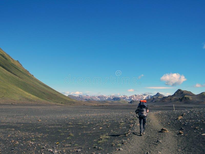 Caminhante masculino experiente que caminha apenas no selvagem com a trouxa pesada no deserto preto, fuga de caminhada de Laugave imagens de stock