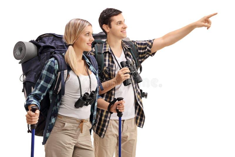 Caminhante masculino que mostra algo na distância ao caminhante fêmea fotografia de stock royalty free