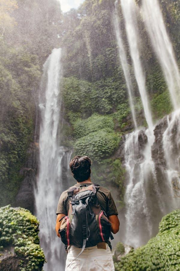Caminhante masculino que olha a cachoeira imagem de stock