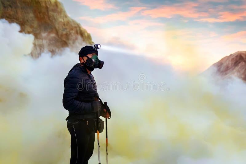 Caminhante na cratera do vulcão ativo Ijen Pares do enxofre, lago tóxico azul vulcânico e alvorecer cor-de-rosa Gunung ijen imagem de stock