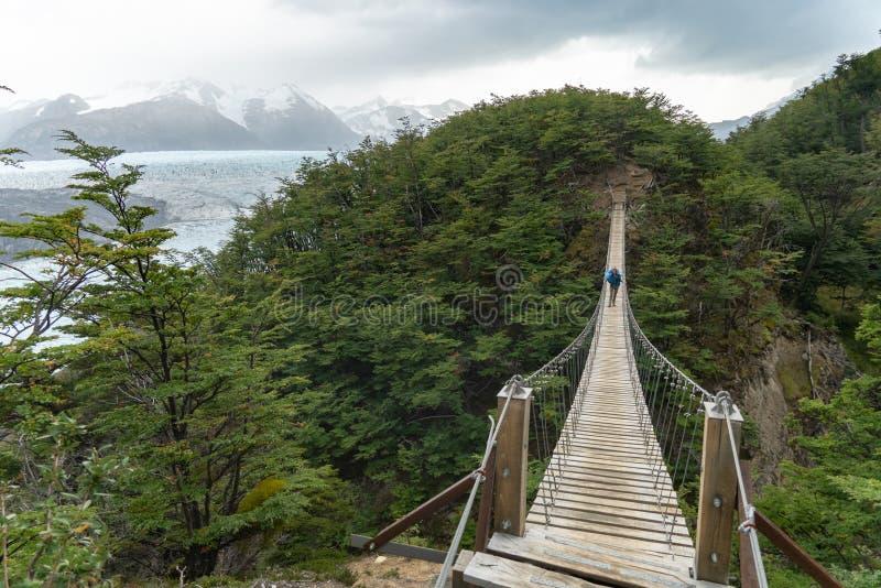 Caminhante na ponte de suspensão longa imagens de stock