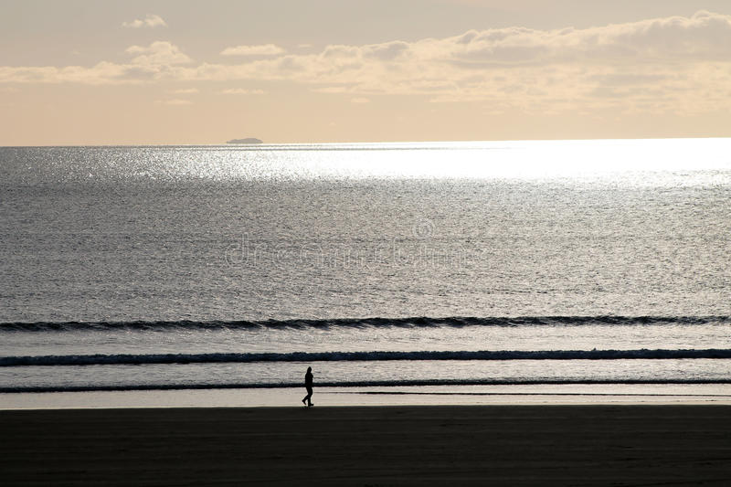 Caminhante na praia com por do sol imagens de stock