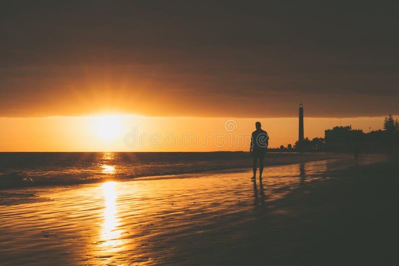 Caminhante no litoral com o farol durante o por do sol em Maspalomas fotos de stock royalty free