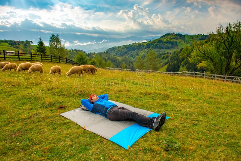 Caminhante novo da montanha que descansa em uma cobertura de nylon impermeável em uma paisagem bonita da montanha, quando dúzias  fotos de stock royalty free