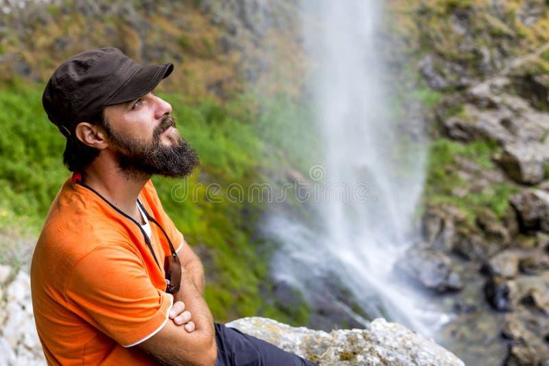 Caminhante novo que senta-se em uma rocha imagem de stock royalty free