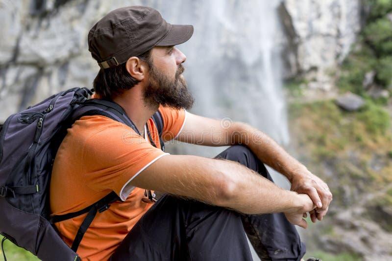 Caminhante novo que senta-se em uma rocha imagens de stock royalty free