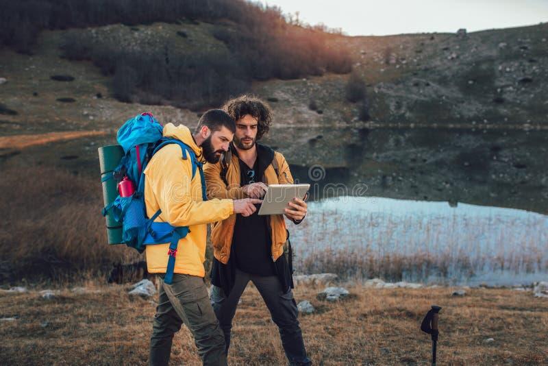 Caminhante perdido que olha a maneira através do mapa na tabuleta digital durante a caminhada foto de stock